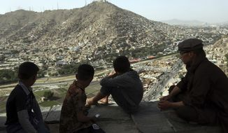 Afghan boys look out over the city of Kabul, Afghanistan, Tuesday, June 5, 2018. (AP Photo/Rahmat Gul) ** FILE **