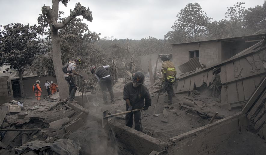 """Firefighters work in the disaster zone blanketed in volcanic ash near the Volcan de Fuego, or """"Volcano of Fire,"""" in the El Rodeo hamlet of Escuintla, Guatemala, Tuesday, June 5, 2018. The fiery volcanic eruption on Sunday in south-central Guatemala killed scores as rescuers struggled to reach people where homes and roads were charred and blanketed with ash. (AP Photo/Rodrigo Abd)"""