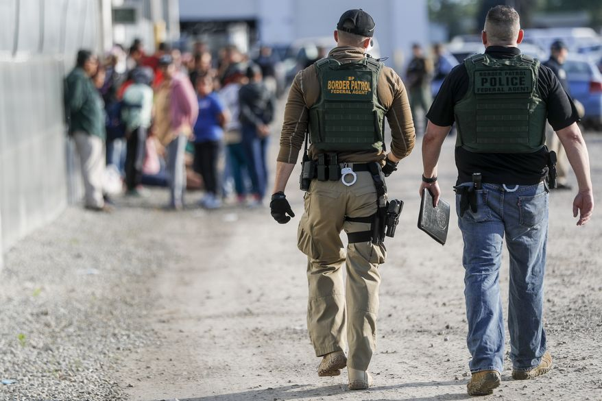 Government agents apprehend suspects during an immigration sting at Corso's Flower and Garden Center, Tuesday, June 5, 2018, in Castalia, Ohio. The operation is one of the largest against employers in recent years on allegations of violating immigration laws. (AP Photo/John Minchillo)