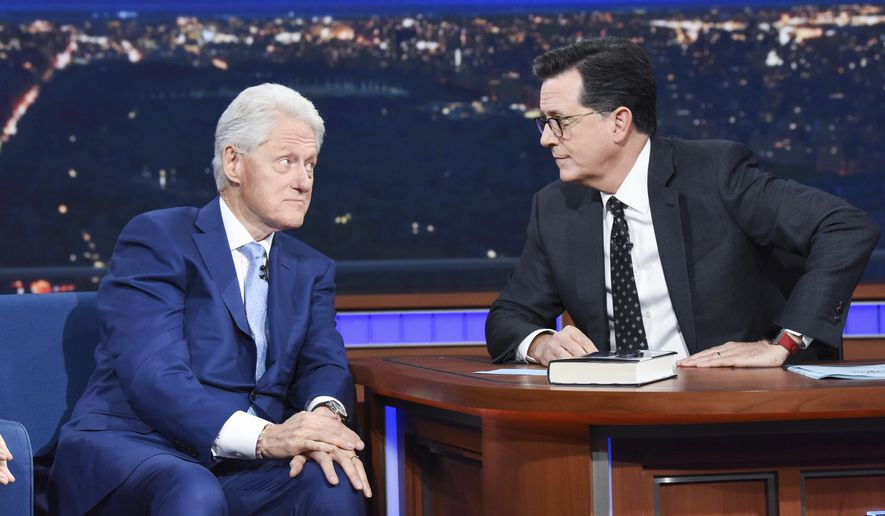 """Former President Bill Clinton, left, appears with host Stephen Colbert while promoting his book """"The President is Missing,"""" on """"The Late Show with Stephen Colbert,"""" Tuesday, June 5, 2018 in New York. (Scott Kowalchyk/CBS via AP) ** FILE **"""