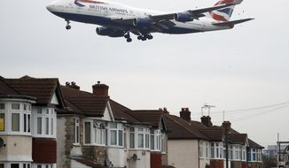 FILE - In this Tuesday, Oct. 25, 2016 file photo, a plane flies over nearby houses as it approaches for landing at Heathrow Airport in London. The British Cabinet on Tuesday June 5, 2018, is expected to approve the construction of a third runway at Heathrow Airport, and to put the long-running issue up for a parliamentary vote.  (AP Photo/Frank Augstein, File)