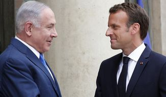 French President Emmanuel Macron, right, welcomes Israel's Prime Minister Benjamin Netanyahu prior to their meeting at the Elysee Palace, in Paris, Tuesday, June 5, 2018. Netanyahu is meeting France's President Emmanuel Macron as part of his European tour, in an effort to rally support from allies over Iran. (AP Photo/Francois Mori)