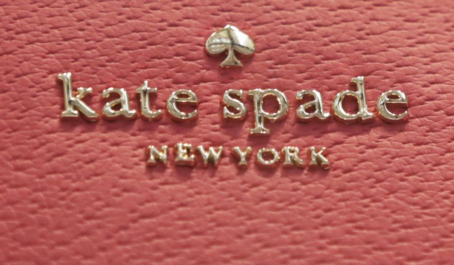 The Kate Spade logo appears on one of her handbags, in her store in New York's Soho neighborhood, Tuesday, June 5, 2018. Spade was found hanged in her apartment Tuesday in an apparent suicide, law enforcement officials said. (AP Photo/Richard Drew)