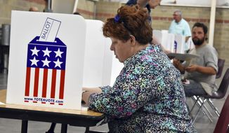 A woman fills out her election ballot at MetraPark Arena in Billings, Mont., Tuesday, June 5, 2018. Turnout was light at polling places in Montana's largest city as most voters already had cast their Primary ballots by mail. (AP Photo/Matthew Brown)