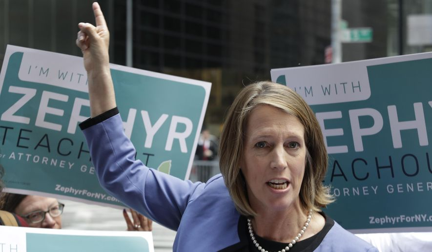 Zephyr Teachout points to Trump Tower while announcing her Democratic Party candidacy for the New York State Attorney General, Tuesday, June 5, 2018, in New York. Teachout faces several candidates in the attorney general race, including New York City Public Advocate Letitia James. James won the endorsement of state Democrats at their convention last month.  (AP Photo/Mark Lennihan)