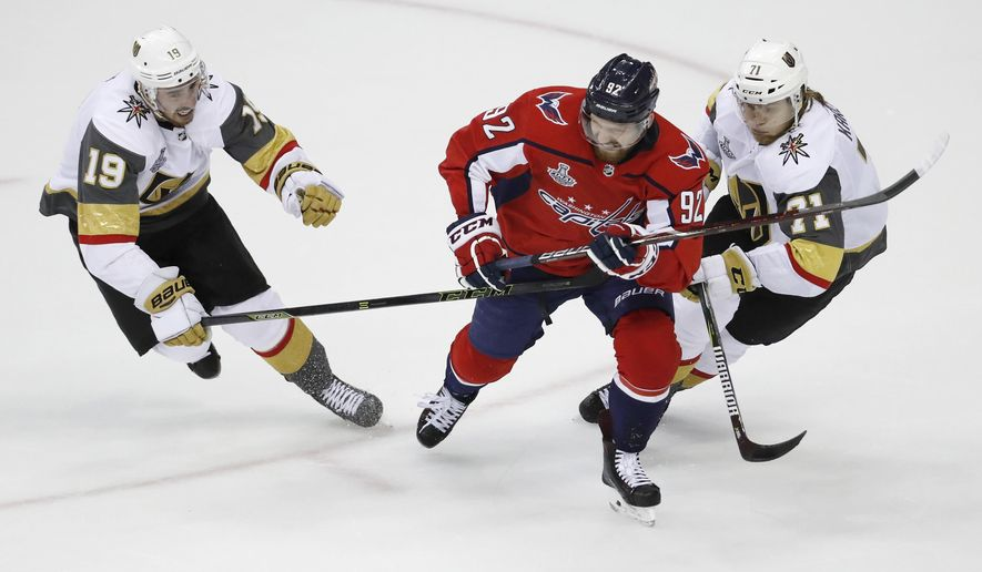 Vegas Golden Knights forwards Reilly Smith, left and William Karlsson, right, of Sweden, chase the puck with Washington Capitals forward Evgeny Kuznetsov (92), of Russia, during the second period in Game 3 of the NHL hockey Stanley Cup Final, Saturday, June 2, 2018, in Washington. (AP Photo/Pablo Martinez Monsivais)