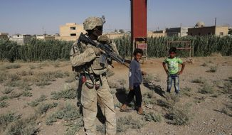 "FILE -- In this July 26, 2017 file photo, a U.S. soldier stands near Syrian children on a road that leads to Raqqa, Syria. Amnesty International, in a report Tuesday, June 5, 2018, accused the U.S. and its allies of showing little regard for civilians' lives while attacking the Syrian city that was once the self-styled capital of the Islamic State group. The report said that the U.S.-led coalition's 2017 assault on Raqqa killed hundreds of civilians and reduced sections of the city to rubble. A coalition spokesman calls the allegations ""absurd and grossly inaccurate."" (AP Photo/Hussein Malla, File)"