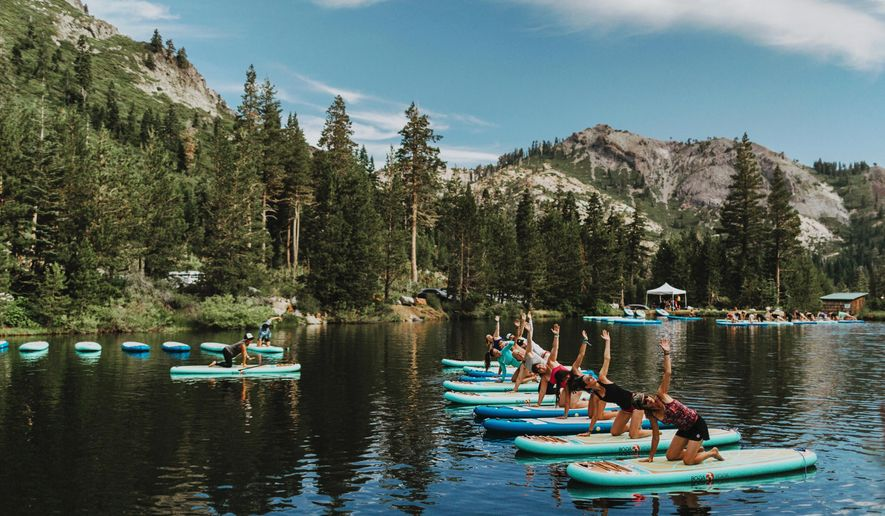 This July 24, 2017 photo provided by Wanderlust, participants work out on paddle boards during Wanderlust Squaw Valley 2017, in North Lake Tahoe, Calif. Wellness tourism is booming, with travelers not just staying fit while on the road, but planning entire trips with a goal of improving their health and well-being. (Amanda Senior/Wanderlust via AP)