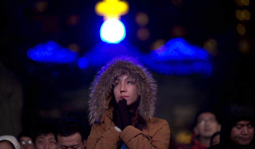 A Chinese woman prays as she takes part in a mass on the eve of Christmas at the South Cathedral official Catholic church in Beijing, China, Wednesday, Dec. 24, 2014. Estimates for the number of Christians in China range from the conservative official figure of 23 million to as many as 100 million by independent scholars, raising the possibility that Christians may rival in size the 85 million members of the ruling Communist Party. (AP Photo/Ng Han Guan)