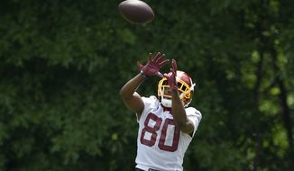 Washington Redskins wide receiver Jamison Crowder leaps to make a catch during an NFL football team practice, Wednesday, June 6, 2018, in Ashburn, Va. (AP Photo/Nick Wass) **FILE**