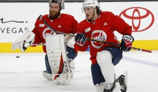Washington Capitals' T.J. Oshie (77) flips the puck in the air as goalie Braden Holtby, left, looks on during an NHL hockey practice Wednesday, June 6, 2018, in Las Vegas. The Capitals lead the Vegas Golden Knights 3-1 in the best-of-seven Stanley Cup Finals series. (AP Photo/Ross D. Franklin)