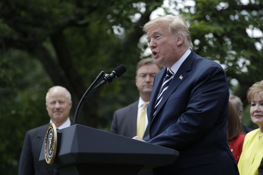 """President Donald Trump participates in a bill signing ceremony for the """"VA Mission Act"""" in the Rose Garden of the White House, Wednesday, June 6, 2018, in Washington. (AP Photo/Evan Vucci)"""
