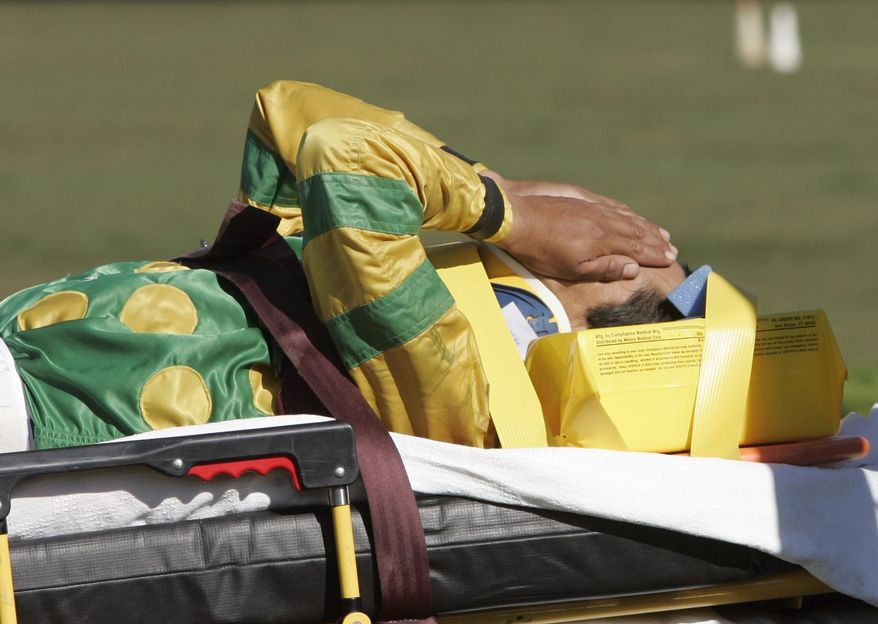 FILE - In this Sept. 1, 2007, file photo, jockey Edgar Prado is taken to an ambulance after falling from Admiral Bird at the conclusion of the seventh race at Saratoga Race Course in Saratoga Springs, N.Y. Doctors with experience treating concussions among jockeys consider it a major issue. In a sport where there is significant attention paid to the health and well-being of horses, jockeys and exercise riders are often an afterthought with inadequate medical care and insurance and limited disability protection. (AP Photo/Mike Groll, File)