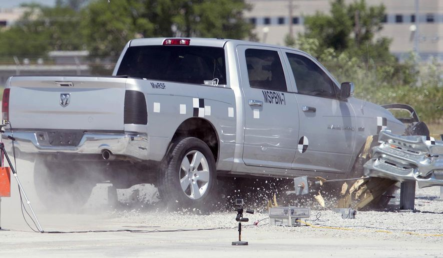 In this June 5, 2018 photo, a Dodge pickup traveling at more than 60 mph decelerates as a median barrier absorbs the energy during a crash test at UNL's Midwest Roadside Safety Facility in Lincoln, Neb. A University of Nebraska-Lincoln engineering team is testing an improved highway safety device to ensure it meets new safety standards the university experts helped write. (Eric Gregory/Lincoln Journal Star via AP)
