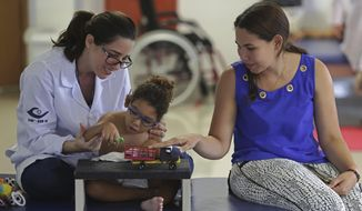 """In this May 3, 2018 photo, Maria de Fatima, right, accompanies her 18-month-son Joaquim, who was born with the Zika-caused microcephaly birth defect, in a manual dexterity therapy session with therapist Catarina Aquino at the Altino Ventura Institute in Recife, Brazil. """"When Joaquim was born I thought he was going to be in a vegetative state forever,"""" said Joaquim's mother. (AP Photo/Eraldo Peres)"""