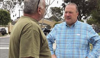 Scott Baugh, a Republican candidate for Congress from Orange County's 48th District, talks with a voter away from a polling place after voting in Huntington Beach, Calif., Tuesday, June 5, 2018. (AP Photo/Krysta Fauria)