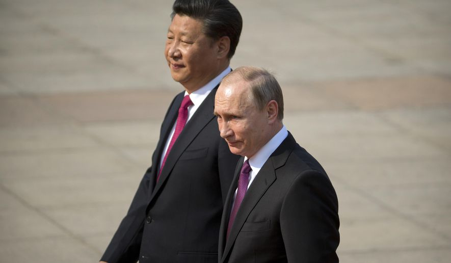 FILE - In this June 25, 2016, file photo, Chinese President Xi Jinping, left, walks with Russian President Vladimir Putin during a welcome ceremony at the Great Hall of the People in Beijing. Just a month after beginning his new term in office, Russian President Vladimir Putin is heading to China for a state visit in June 2018, underscoring how mounting U.S. pressure is drawing the two countries increasingly close. (AP Photo/Mark Schiefelbein, File)
