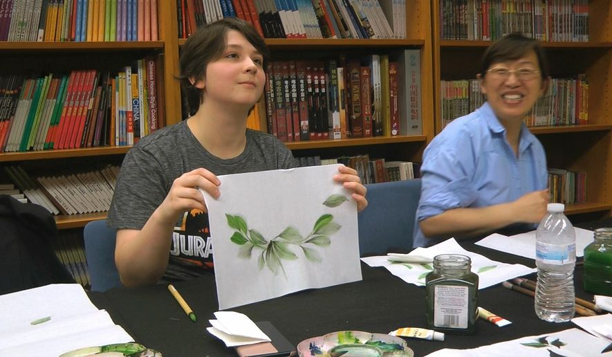 Undergraduate student Moe Lewis, left, shows her watercolor painting of peony leaves at a traditional Chinese painting class at the Confucius Institute at George Mason University in Fairfax, Va., on May 2, 2018. U.S. lawmakers are pushing for tighter regulation or even closure of the more than 100 Chinese Confucius Institutes set up on campuses across America. But for university students, they offer a chance to learn about Chinese language and art. (AP Photo/Matthew Pennington)