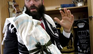 In this Wednesday, May 30, 2018, Rabbi Arie Zeev Raskin, the leader of Cyprus' 3,500-strong Jewish community, holds a rare 110 year-old Torah scroll that comes from Bohemia in what is now the western-most pat of the Czech Republic, at a synagogue inside Cyprus' Jewish Community Center in the town of Larnaca. The scrolls will be put on display in a new museum on the eastern Mediterranean island-nation that its founders envision as a bridge-builder to the Arab world and beyond, a place where visitors who may never set foot in Israel can learn about the Jewish faith, the Holocaust and the tumultuous beginnings of the Jewish state. (AP Photo/Petros Karadjias)