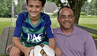 Bennett Wehibe, 12, left, and his father, Steve, POSE for a photo Thursday May 31, 2018, in the backyard of their West Lampeter Township, Pa. home. Bennett will represent the U.S. this week at the Football for Friendship soccer program in Moscow.  (Blaine T. Shahan/LNP via AP)