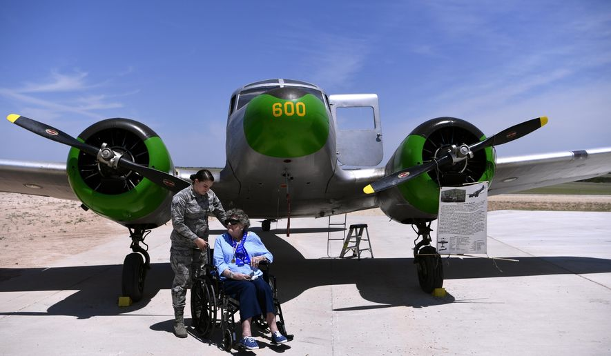In a May 26, 2018 photo, Senior Airman Tiffany Schockley of Dyess Air Force Base waits with Dorothy Lucas in front of a Cessna UC-78 Bobcat at the WASP Homecoming in Sweetwater, Texas. Lucas was a member of the Women's Airforce Service Pilots and trained at Avenger Field in 1944. (Ronald W. Erdrich/The Abilene Reporter-News via AP)