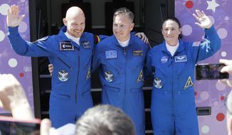 U.S. astronaut Serena Aunon-Chancellor, right, Russian cosmonaut Sergey Prokopyev, center, and German astronaut Alexander Gerst, members of the main crew to the International Space Station (ISS), wave near a bus from a hotel prior the launch of Soyuz-FG rocket at the Russian leased Baikonur cosmodrome, Kazakhstan, Wednesday, June 6, 2018. (AP Photo/Dmitri Lovetsky)