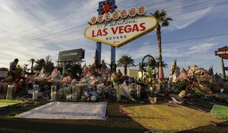 FILE - In this Oct. 16, 2017 file photo, people visit a makeshift memorial for victims of the mass shooting in Las Vegas. Police are scheduled to release more public records under court order from the investigation of the shooting on the Las Vegas Strip last October that was the deadliest incident of its kind in the nation's modern history. (AP Photo/John Locher, File)