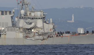 The damaged USS Fitzgerald is seen near the U.S. Naval base in Yokosuka, southwest of Tokyo, after the U.S. destroyer collided with the Philippine-registered container ship ACX Crystal in the waters off the Izu Peninsula Saturday, June 17, 2017. The USS Fitzgerald was back at its home port in Japan after colliding before dawn Saturday with the container ship four times its size, while the coast guard and Japanese and U.S. military searched for seven sailors missing after the crash. (AP Photo/Eugene Hoshiko)
