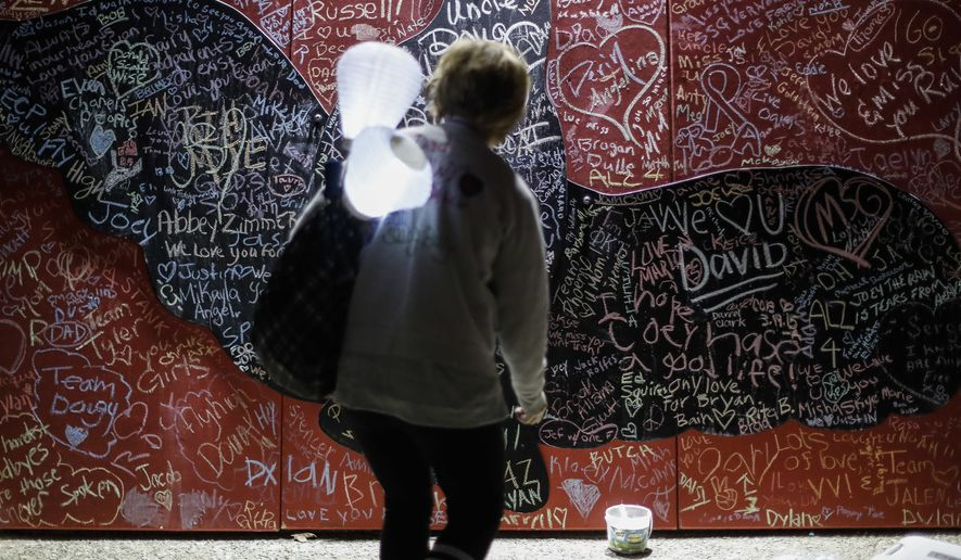 Jill Taylor, of Hamilton, Ohio, who lost her father Gary B. Shepherd taking his own life in 2011, steps up to a message board decorated with notes for loved ones during an Out of the Darkness Walk event organized by the Cincinnati Chapter of the American Foundation for Suicide Prevention in Sawyer Point park, Sunday, Oct. 15, 2017, in Cincinnati. Hundreds of supporters gathered to draw attention to and raise funds for the prevention of suicide that ranks as the tenth leading cause of death in the United States overall according to the Centers for Disease Control (CDC). (AP Photo/John Minchillo)