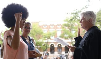 Mariah Parker takes her oath of office for County Commissioner District 2 with her hand on the autobiography of Malcolm X and her mother Mattie Parker by her side on the steps of City Hall in downtown Athens, Ga., Tuesday, June 5, 2018. Parker filled the county commissioner seat vacated by Harry Sims who left his seat to run for mayor. She won the election for District 2 by 13 votes. (Joshua L. Jones/Athens Banner-Herald via AP)