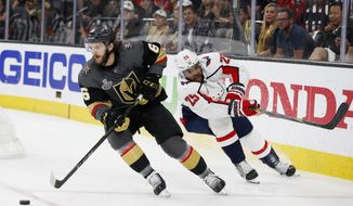 Vegas Golden Knights defenseman Colin Miller, left, moves the puck as Washington Capitals right wing Devante Smith-Pelly puts pressure on him during the first period in Game 5 of the NHL hockey Stanley Cup Finals on Thursday, June 7, 2018, in Las Vegas. (AP Photo/John Locher)