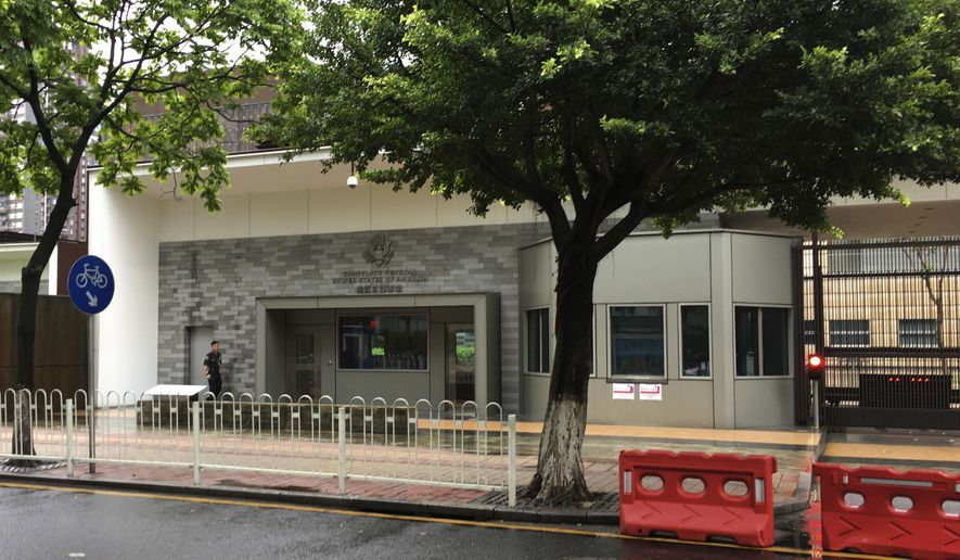 """A security person walks outside the U.S. consulate building in Guangzhou in south China's Guangdong province, Thursday, June 7, 2018. The United States has evacuated several more government workers out of the southern Chinese city of Guangzhou after medical testing revealed they might have been affected by unexplained health incidents that have already hurt U.S. personnel in Cuba, the State Department said Wednesday. State Department spokeswoman Heather Nauert said """"a number of individuals"""" have been brought to the U.S. They are in addition to a U.S. worker in Guangzhou who was evacuated earlier, as the Trump administration had already disclosed. (AP Photo/Kelvin Chan)"""