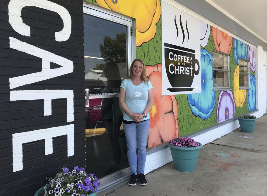 In this May 23, 2018 photo, Melissa Schwalenberg poses outside Coffee with Christ, her new  cafe and meeting place in Belleville, Ill. After nearly 20 years of teaching elementary school in the metro-east, Schwalenberg is taking a long coffee break to give back to local kids and adults in a different way. Not far from the cash register, there's a colorful wall of sticky notes where patrons can promote kindness. Each handwritten note offers a free oatmeal, free yogurt, free drink or meal credit to a person in need of a pick-me-up, or someone who might not have enough money to pay their bill. (Cara Anthony /Belleville News-Democrat, via AP)