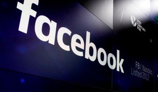 In this March 29, 2018, file photo, the logo for Facebook appears on screens at the Nasdaq MarketSite in New York's Times Square. (AP Photo/Richard Drew, File)