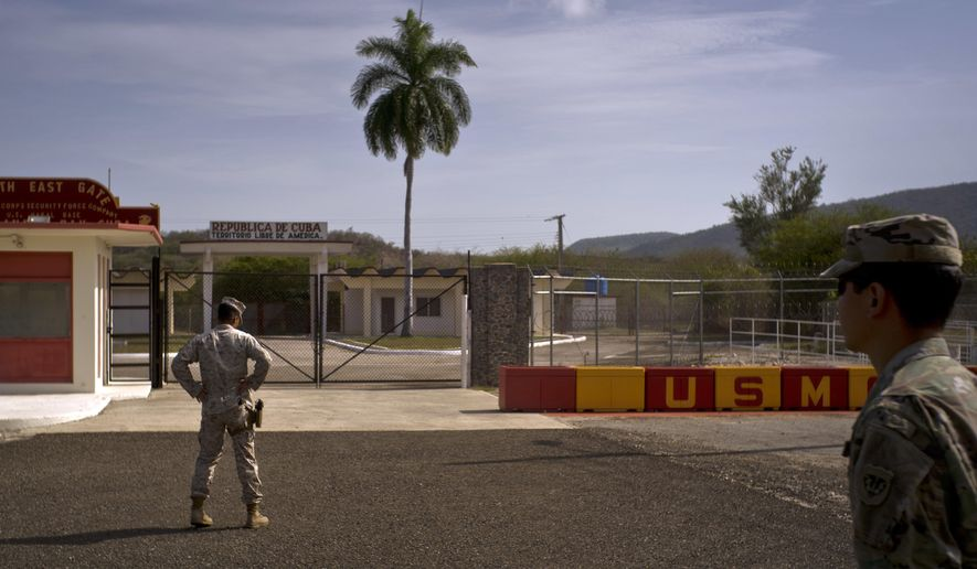 In this Wednesday, June 6, 2018 photo, reviewed by U.S. military officials, an Army soldier, right, and a Marine stand in front of the gates that separate the Cuban side from the Guantanamo Bay U.S. Naval Base. The White House has endorsed a proposal for a new unit, which would have cell doors wide enough for wheelchairs and hospice beds and communal areas so elderly prisoners could help each other as they grow old. (AP Photo/Ramon Espinosa)