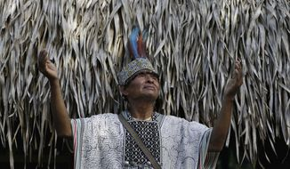 In this May 5, 2018 photo, Shaman Pablo Flores raises his hands to the sky before the beginning of an ayahuasca session, in Nuevo Egipto, a remote village in the jungles of Peru. Flores performs ayahuasca sessions for tourists. He does not charge for his services but does accept donations. (AP Photo/Martin Mejia)