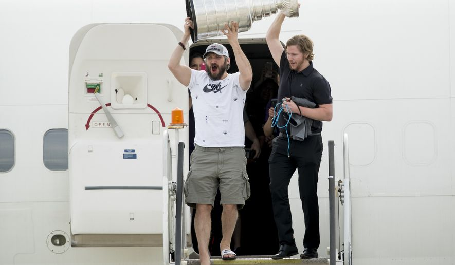 Washington Capitals left wing Alex Ovechkin, left, of Russia, and center Nicklas Backstrom, of Sweden, right, hold up the Stanley Cup as the Capitols arrive at Dulles International Airport in Sterling, Va., Friday, June 8, 2018, the day after defeating the Vegas Golden Knights in Game 5 of the NHL hockey Stanley Cup Finals. (AP Photo/Andrew Harnik)