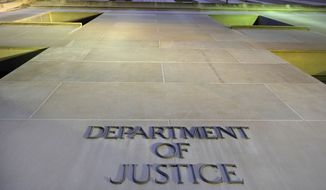 In this May 14, 2013, file photo, the Department of Justice headquarters building in Washington is photographed early in the morning. (AP Photo/J. David Ake, File)