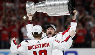 Washington Capitals left wing Alex Ovechkin, of Russia, hands the Stanley Cup to center Nicklas Backstrom, of Sweden, after the Capitals defeated the Golden Knights 4-3 in Game 5 of the NHL hockey Stanley Cup Finals Thursday, June 7, 2018, in Las Vegas. (AP Photo/John Locher) ** FILE **