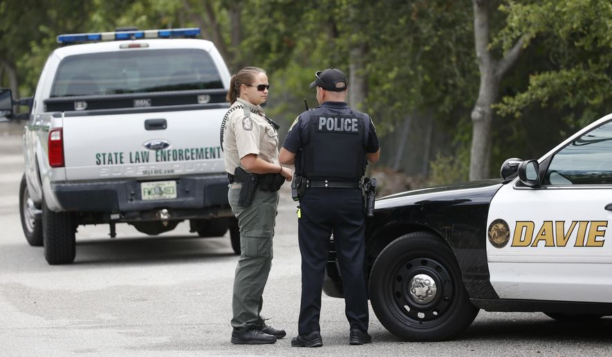 Law enforcement officers gather at the entrance of Silver Lakes Rotary Nature Park, Friday, June 8, 2018, in Davie, Fla. Someone called police after seeing a woman who was walking her dog in the park being dragged into a lake by an alligator. (AP Photo/Wilfredo Lee)