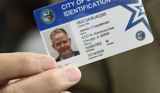 Alderman James Cappleman holds his CityKey ID card, Friday, June 8, 2018, in Chicago. The city of Chicago is sending out staffers into various communities to get the municipal ID cards into the hands of undocumented immigrants, homeless people, senior citizens and others who often find it hard to obtain a valid form of identification. Officials hope that in a couple of years more than 100,000 Chicago residents will have the cards that can be used to register to vote and do things like check out a book from the library. (AP Photo/Annie Rice)