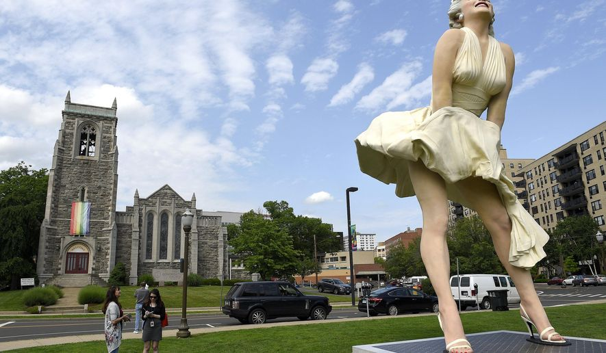 """This Thursday, June 7, 2018 photo shows  Seward Johnson's """"Forever Marilyn"""" sculpture in Latham Park in Stamford, Conn.  The 26-foot statue that was newly installed in the park is scandalizing some because her rear end is facing the entrance of the First Congregational Church.  (Matthew Brown/Hearst Connecticut Media via AP)"""