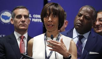 Baltimore Mayor Catherine Pugh addresses a gathering during the annual meeting of the U.S. Conference of Mayors in Boston, Friday, June 8, 2018. More than 250 city executives gathered to discuss their concerns including infrastructure, school safety, immigration and the economic future of cities. With Pugh are Los Angeles Mayor Eric Garcetti, left, and Columbia, S.C., Mayor Steve Benjamin. (AP Photo/Charles Krupa)