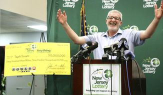 Tayeb Souami, of Little Ferry, gestures as he iss introduced as the $351.3 million Powerball winner, Friday, June 8, 2018, in Trenton, N.J. (Chris Pedota/The Record via AP)