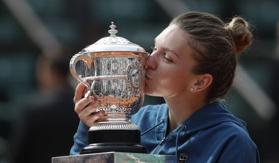 Romania's Simona Halep kisses the trophy as she celebrates winning the final match of the French Open tennis tournament against Sloane Stephens of the U.S. in three sets 3-6, 6-4, 6-1, at the Roland Garros stadium in Paris, France, Saturday, June 9, 2018. (AP Photo/Alessandra Tarantino)