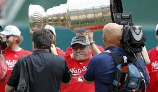 Washington Capitals head coach Barry Trotz lifts the Stanley Cup before a baseball game between the Washington Nationals and the San Francisco Giants at Nationals Park, Saturday, June 9, 2018, in Washington. (AP Photo/Alex Brandon) ** FILE **