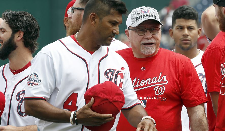 Washington Nationals manager Dave Martinez (4) and Washington Capitals head coach Barry Trotz, second from right, talk on the field before a baseball game between the Washington Nationals and the San Francisco Giants at Nationals Park, Saturday, June 9, 2018, in Washington. (AP Photo/Alex Brandon)