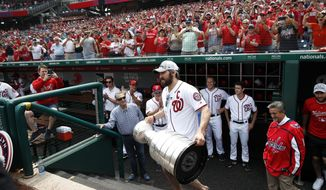 Washington Capitals' Alex Ovechkin, from Russia, walks to the field with the Stanley Cup, followed by Capitals owner Ted Leonsis, right, before a baseball game between the Washington Nationals and the San Francisco Giants at Nationals Park, Saturday, June 9, 2018, in Washington. (AP Photo/Alex Brandon)