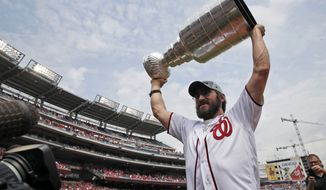 Washington Capitals' Alex Ovechkin, from Russia, lifts the Stanley Cup on the field before a baseball game between the Washington Nationals and the San Francisco Giants at Nationals Park, Saturday, June 9, 2018, in Washington. (AP Photo/Alex Brandon)
