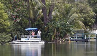 A couple looks out from a pontoon boat on one of the lakes at Silver Lakes Rotary Nature Park, Friday, June 8, 2018, in Davie, Fla. Authorities worked Friday to capture an alligator in a Florida pond after a witness' report led police to believe the animal may have dragged a woman into the water. (AP Photo/Wilfredo Lee)